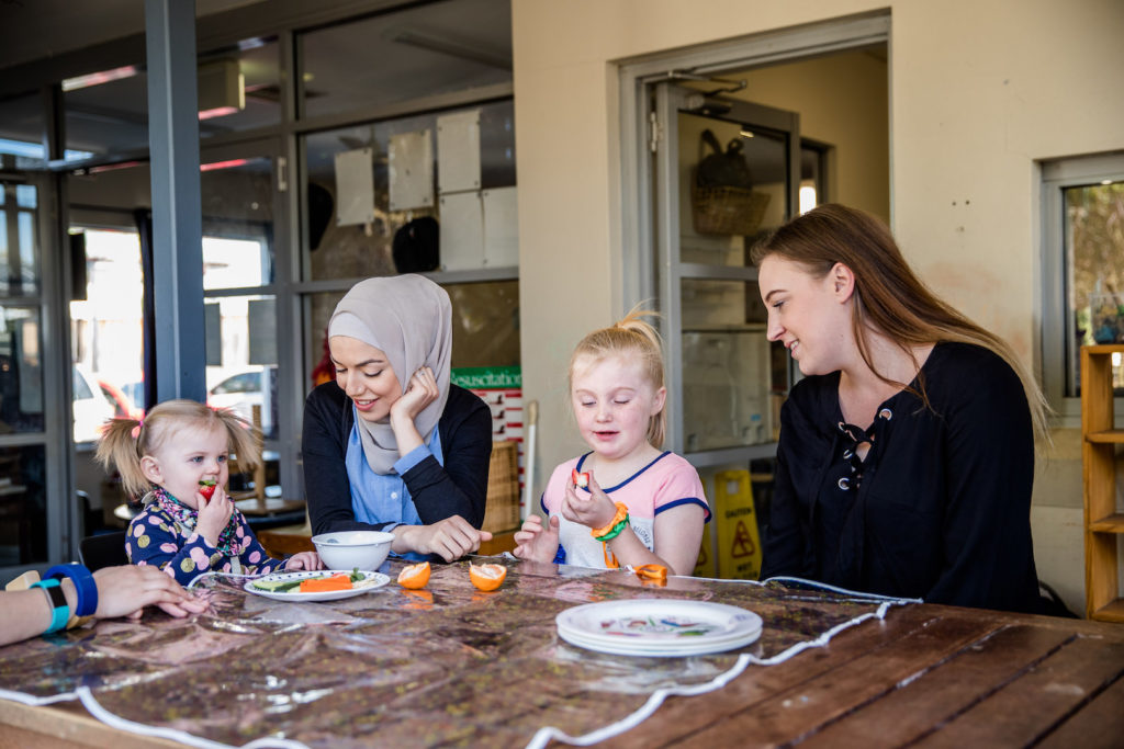 Our Dietetic and Nutrition specialist at a table with children eating