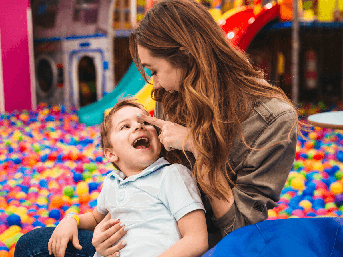 woman and child seated in a ball pit and making eye contact