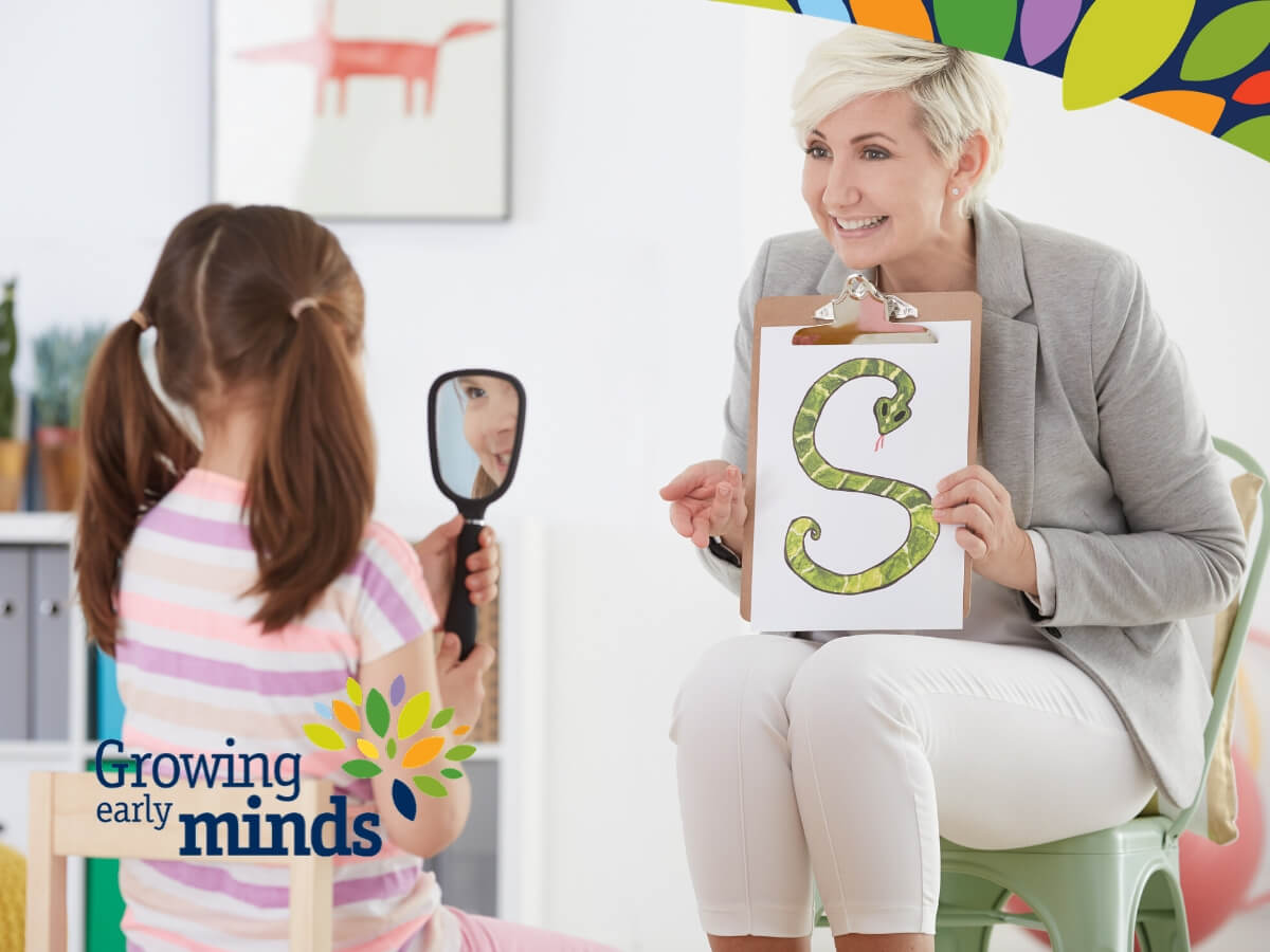 adult holding a clipboard with the letter S on it, with a little girl holding a mirror practicing sounds